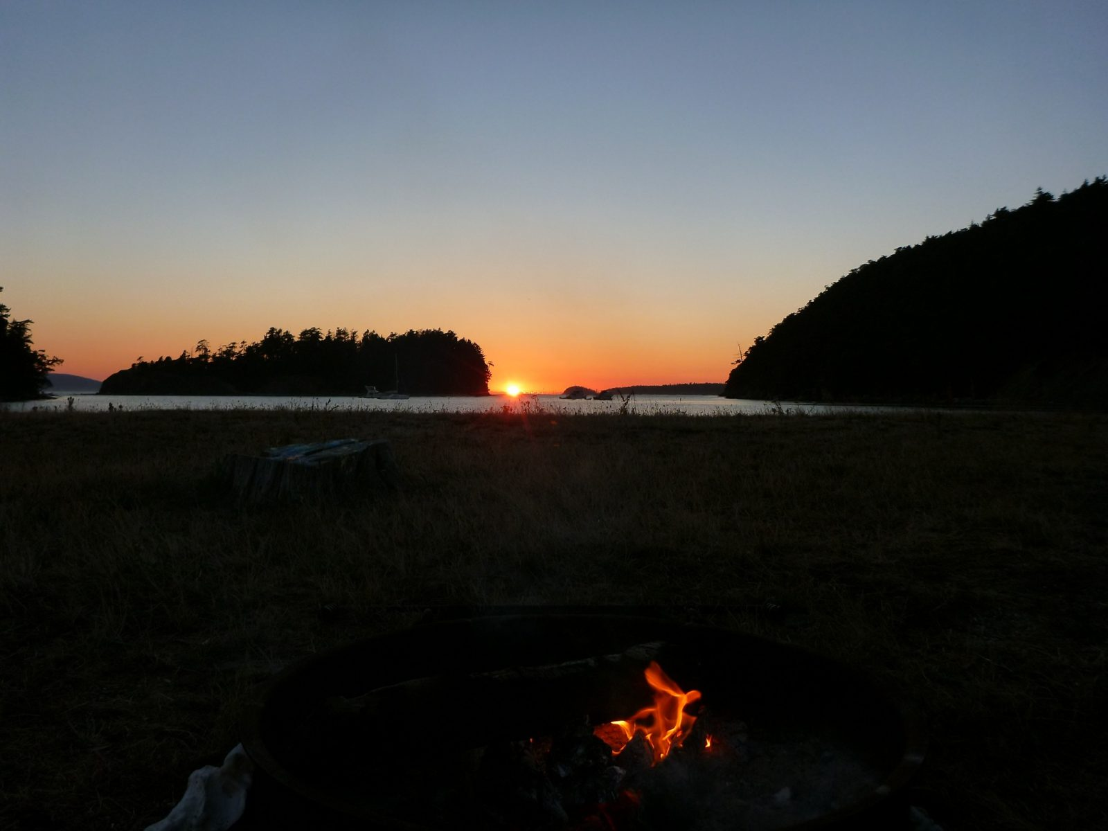 a campfire on the beach on Sucia Island. In the distance the sun is setting below the water and between two forested islands.