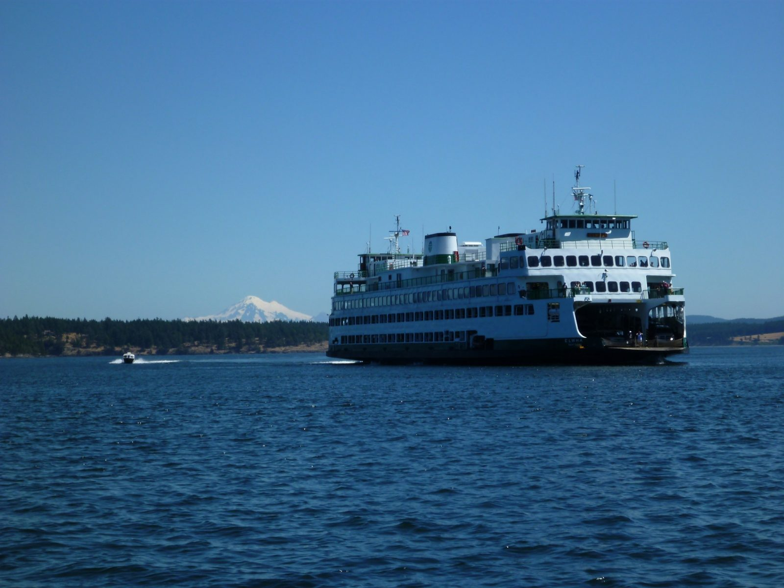 A white Washington State ferry with an open front end showing cars with a small powerboat next to it. There is a forested island in the background and a high snow capped mountain