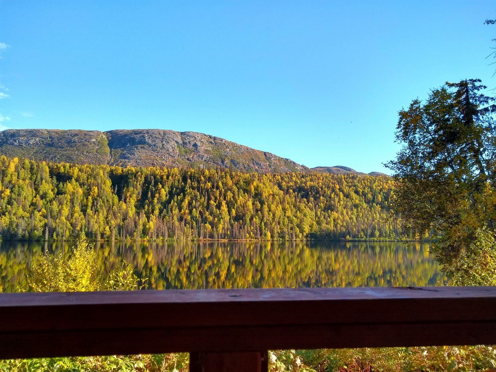 A wooden railing in the foreground with a calm lake surronded by trees and hills