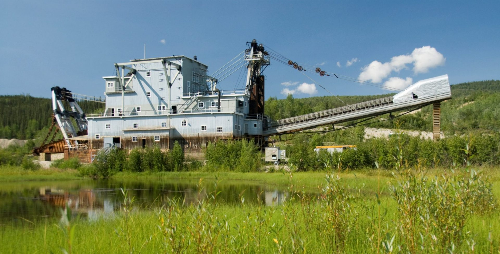 A large gold dredge in a green field with a pond and mountains in the background. The dredge looks like a 5 story metal building with a long arm sticking out one side and more machinery in the back