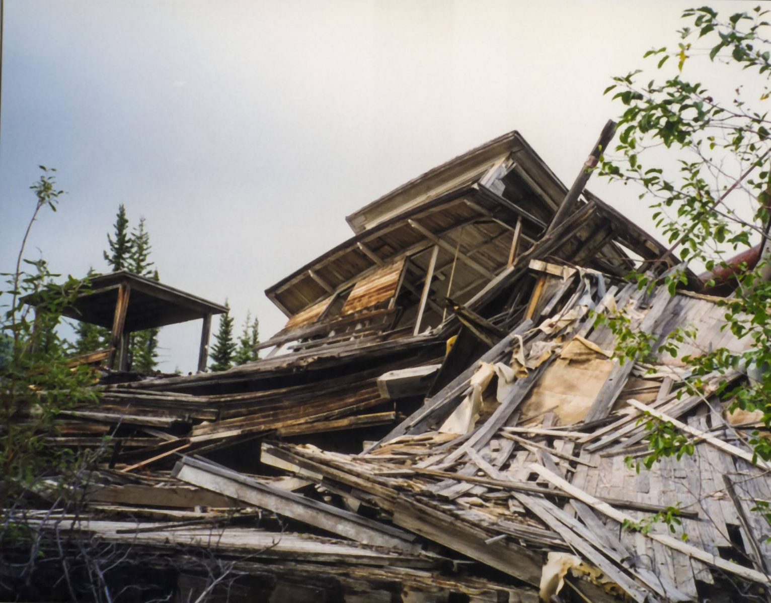 A unique thing to do in dawson city is visit the paddle wheeler graveyard, a collection of crushed old ships damaged by the river. A pile of crumpled wood takes up the photo, an old pilot house partially collapsed can be seen at the top of the pile
