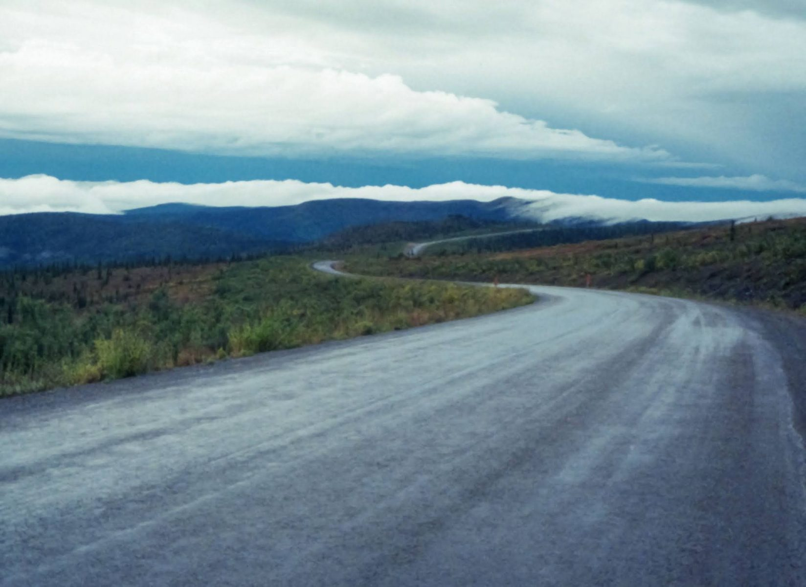 A gravel road winds along an open ridge surrounded by shrubs and distant mountains. It's a rainy day
