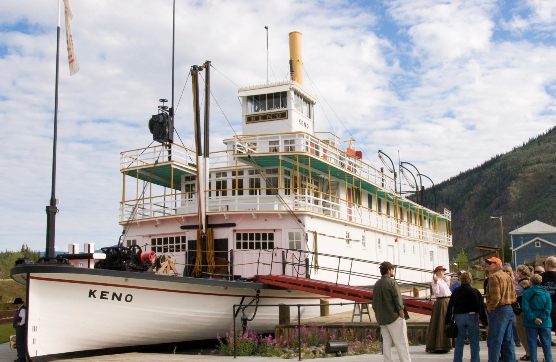 A restored paddle wheeler in downtown Dawson City. It's white with red and green trim and called the Keno. A group of people on a tour are standing in front of it