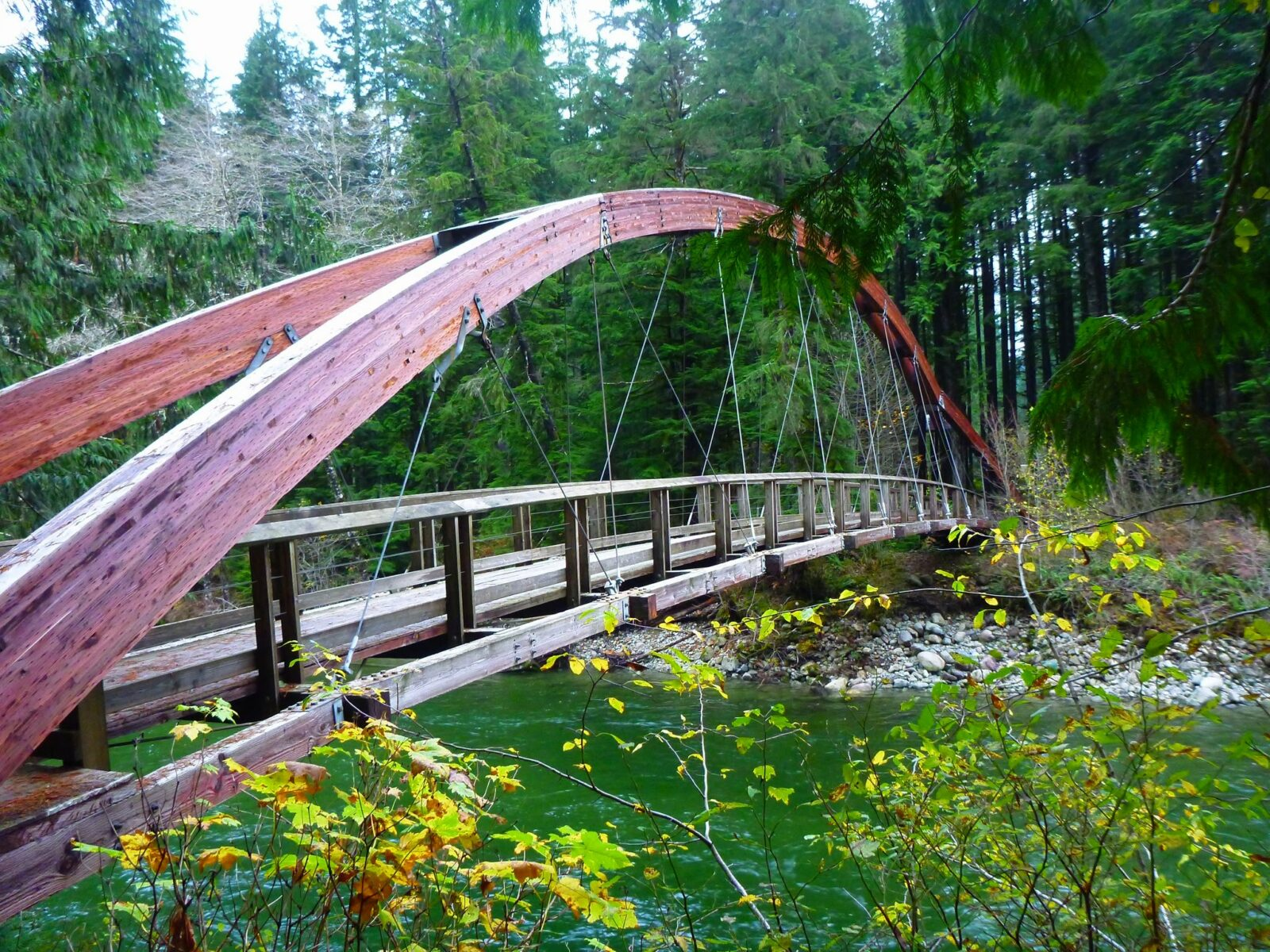 A wooden and cable bridge over the middle fork snoqualmie river, one of the many hikes near north bend washington, with an arched wooden top over a fast moving river. The bridge is surrounded by evergreen trees and bushes.