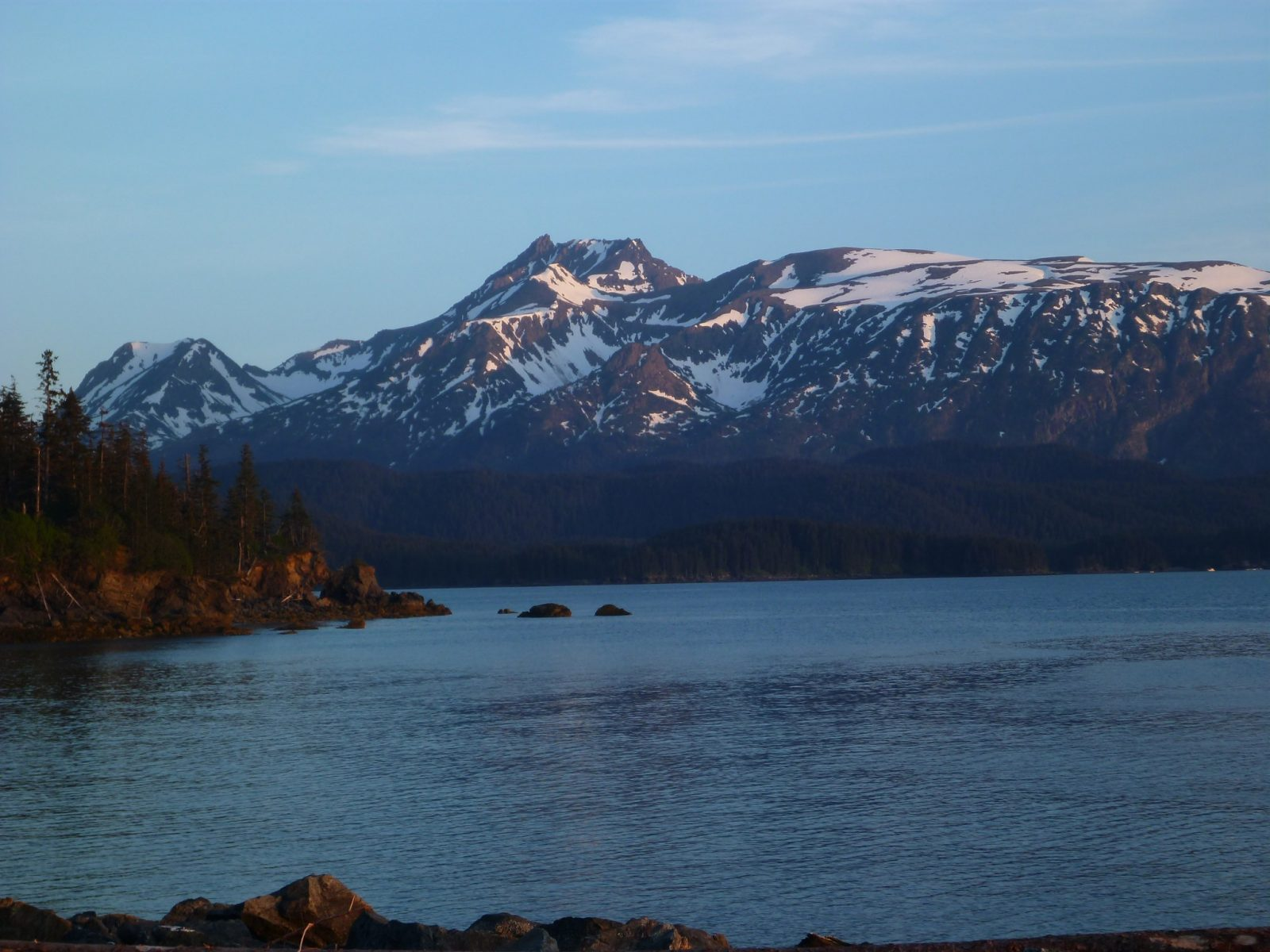 Evening sun hits mountains with lingering snow across a bay. In the foreground are trees and a rocky shore