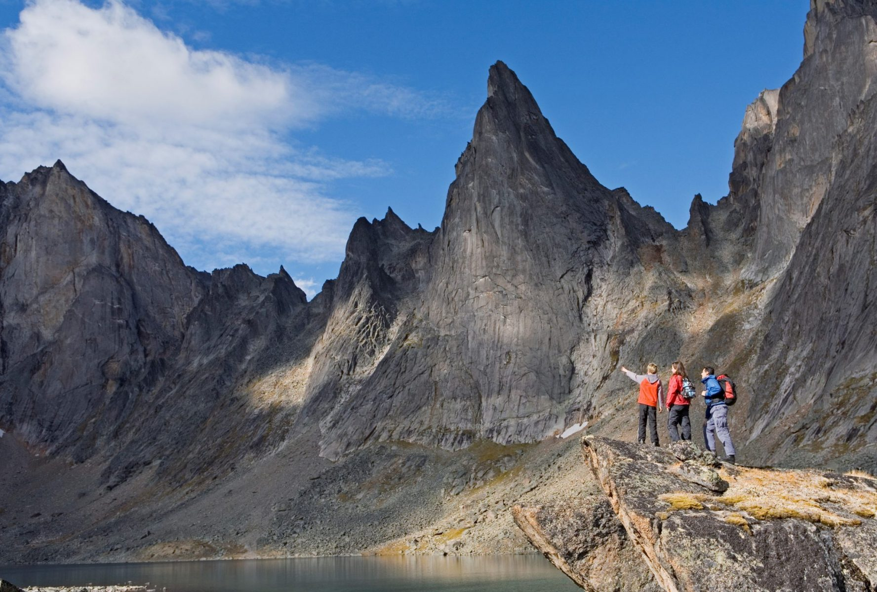 Three hikers stand on a rock next to a lake surrounded by high jagged mountains in Tombstone Territorial Park
