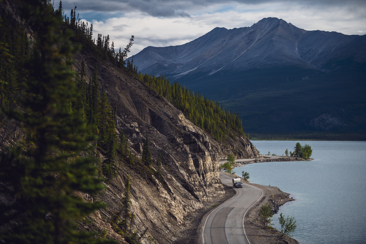 A two lane paved road winds between a forested hillside and a lake with mountains in the background on the drive to alaska