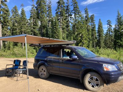 A blue SUV parked in the forest with an awning extended from the roof. There are two camp chairs parked under it