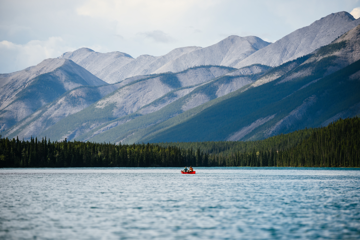 Muncho Lake along the drive to alaska with a distant canoe and two people paddling. On the other side of the lake is forest and high mountains