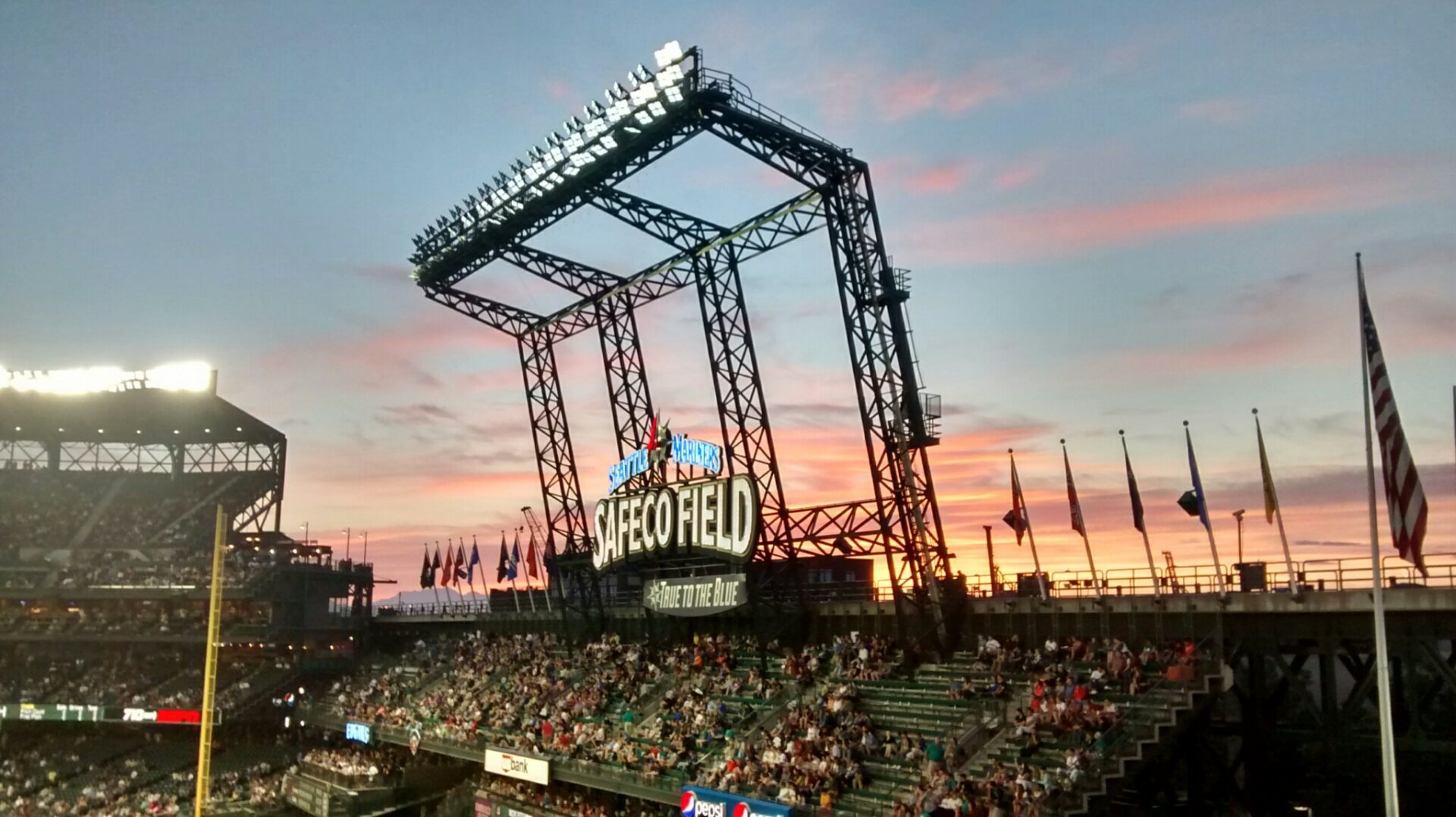 Safeco Field in Seattle. The sun is setting and the roof is open. The lights have just come on. There are fans and flags and a steel structure holding the lights.