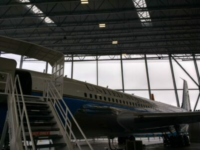 An old Air Force airplane in a hanger with stairs going up to the door