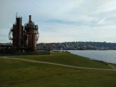 Seattle parks are an important part of a Seattle itinerary. This is gasworks park, with old rusted steam equipment sitting on a grassy hill with a trail going by. In the background is Lake Union, an urban lake in Seattle