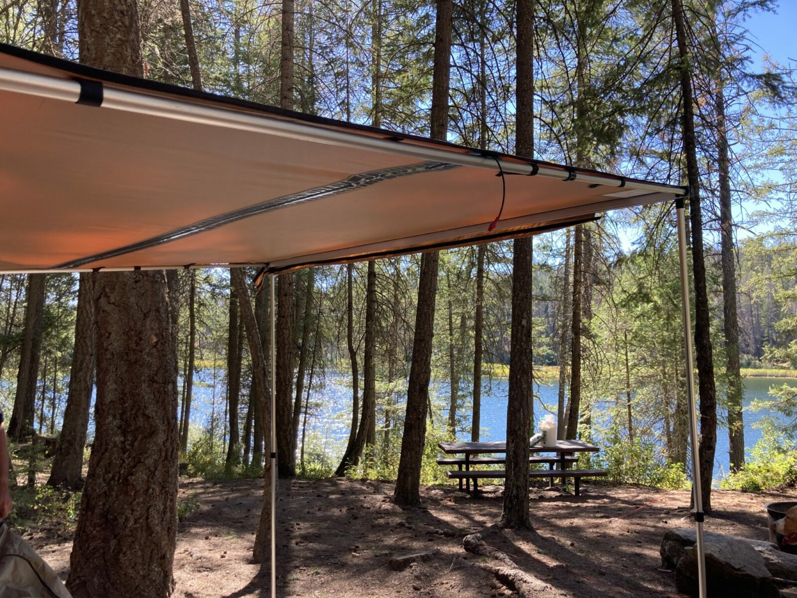 A roof rack awning set up and providing shade in a forested campground next to a lake