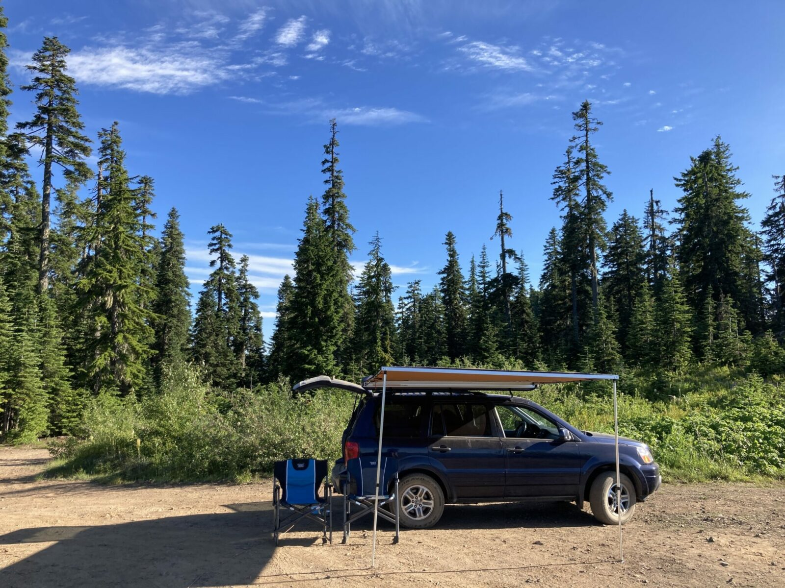 A blue SUV parked on a dirt open area in the forest surrounded by bushes. The rear hatch of the SUV is open and a roof top awning is set up on the side. There are two camp chairs sitting next to it.