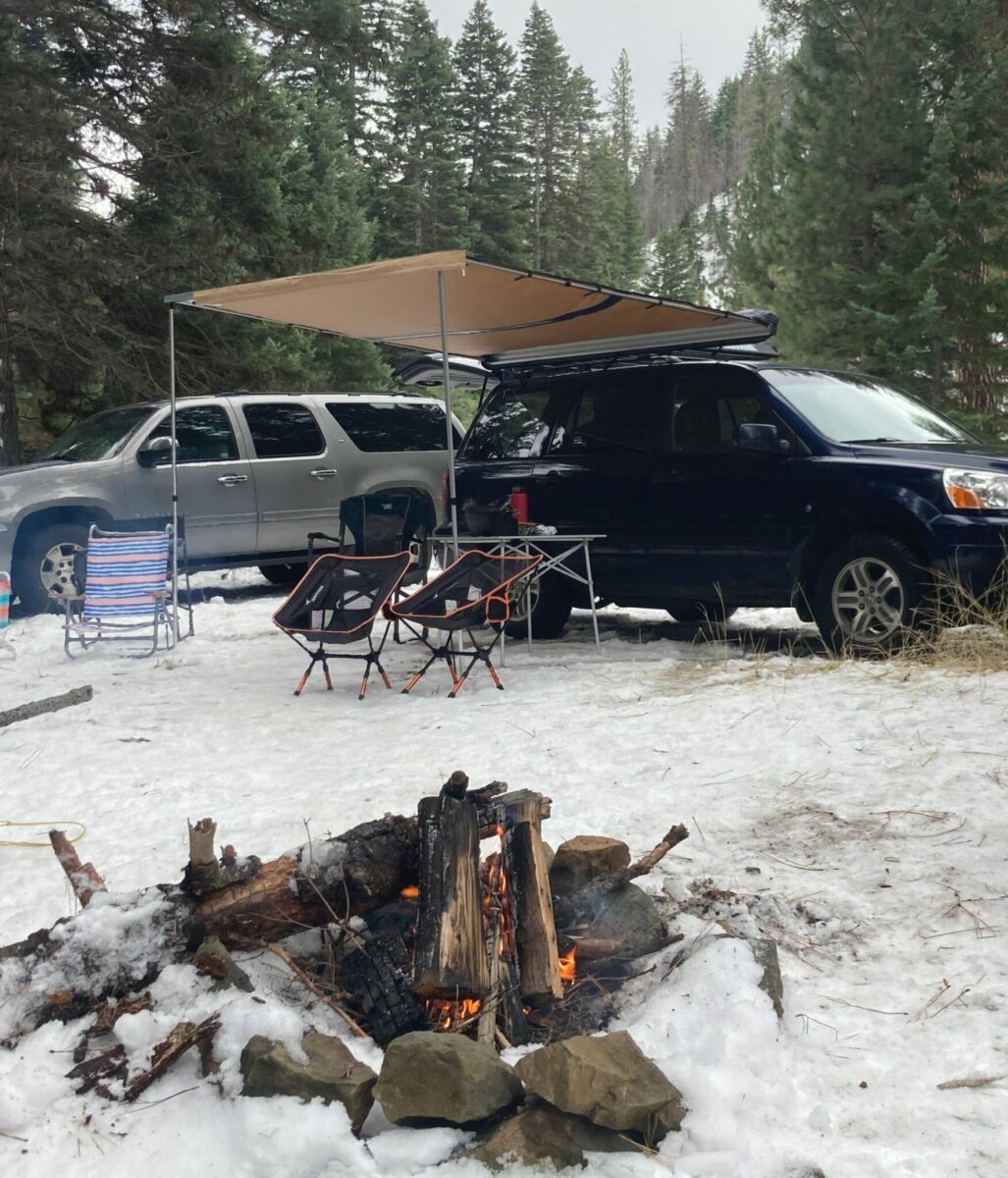 A gray SUV parked near a blue SUV. The blue SUV has a roof top awning set up on the side with a table and camp chairs under it. There is snow on the ground and in the foreground is a campfire