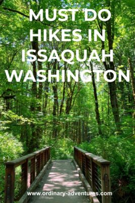 A green forest is green upon green with spring growth. In the middle of the trees and undergrowth, a brown bridge over a creek leads into the forest. Test reads: Must do hikes in Issaquah Washington