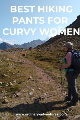 A trail in a meadow next to a higher mountain with mountains in the distance and a person on the trail wearing gray hiking pants, a green tank top, a hat and a backpack and carrying hiking poles. Text reads: best hiking pants for curvy women