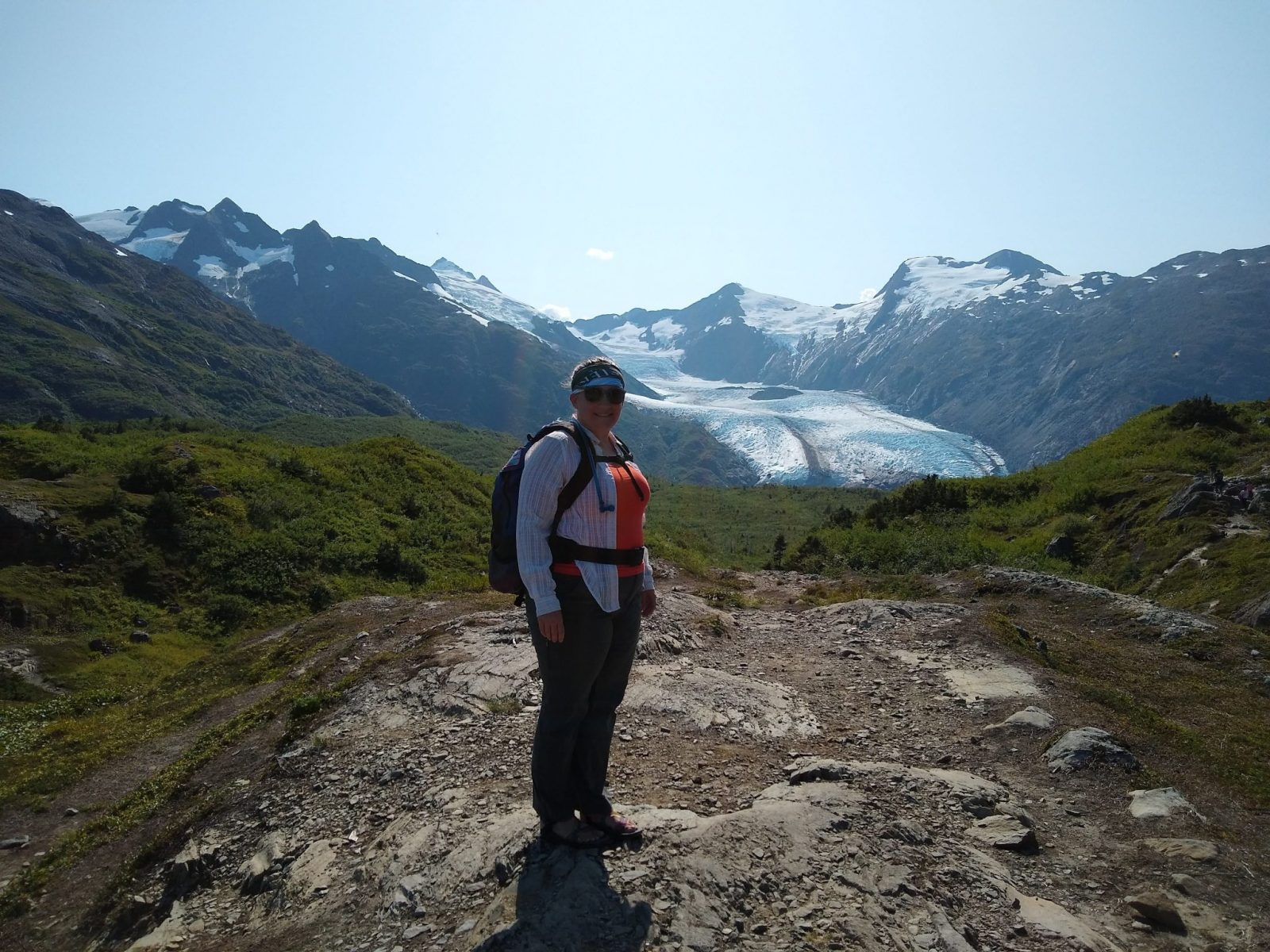 A woman on a rocky trail in a meadow with mountains and a glacier in the background wearing hiking pants, a tank top, a long sleeve shirt, a backpack and sunglasses