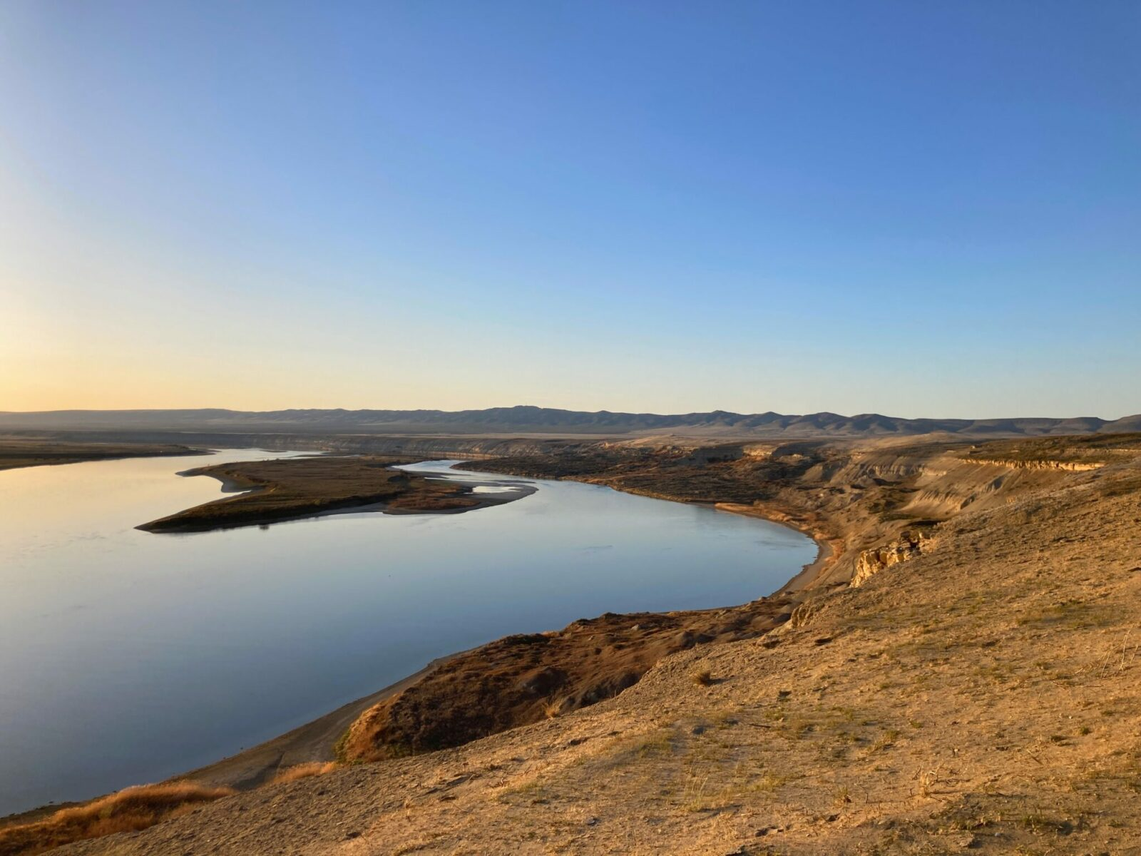 Hanford Reach is a section of the Columbia River in Eastern Washington. The river and an island in it are seen from the bluffs above, surrounded by bluffs and distant mountains at sunset on a sunny day