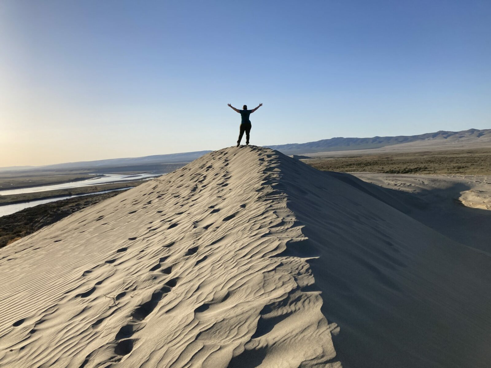 The top of a sand dune at Hanford Reach in a desert in late afternoon. A person stands on the top of the dune with their hands in the air. In the distance are brown mountains and a river
