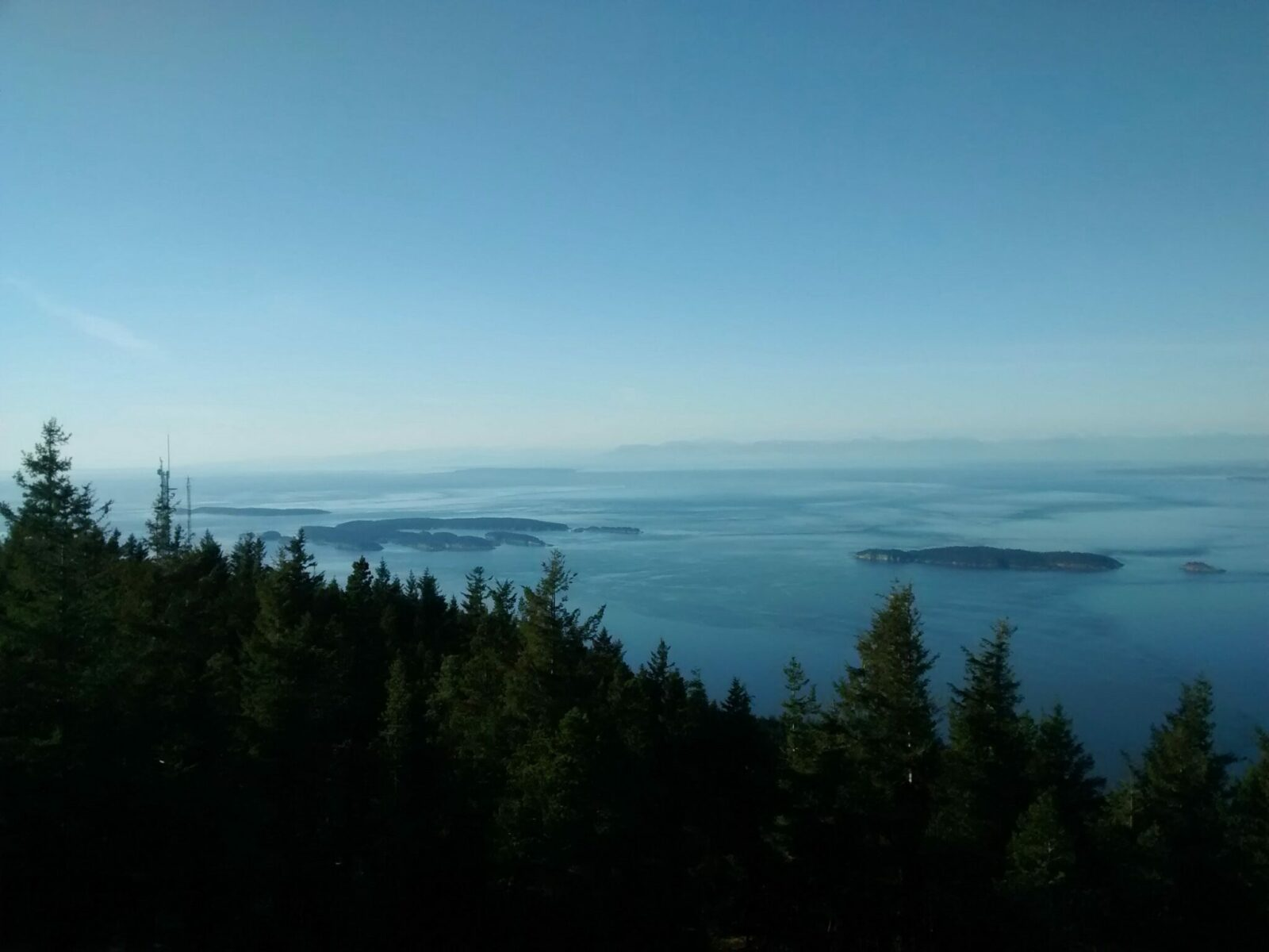 Sucia Island seen from the summit of Mt Constitution on Orcas Island. There are other islands visible in the water and a forest in the foreground and distant mountains in the hazy background