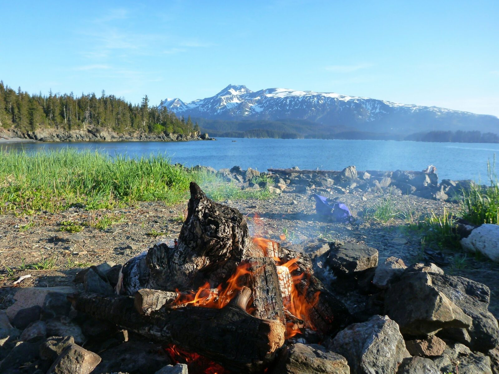 A campfire in the foreground on a rocky and grassy beach along a small bay. Across the bay there are forested hillsides and higher mountains with lingering snow