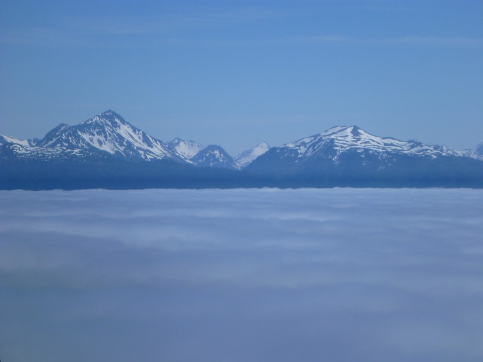 Mountains with lingering snow rise above a thick cloud layer on a sunny day