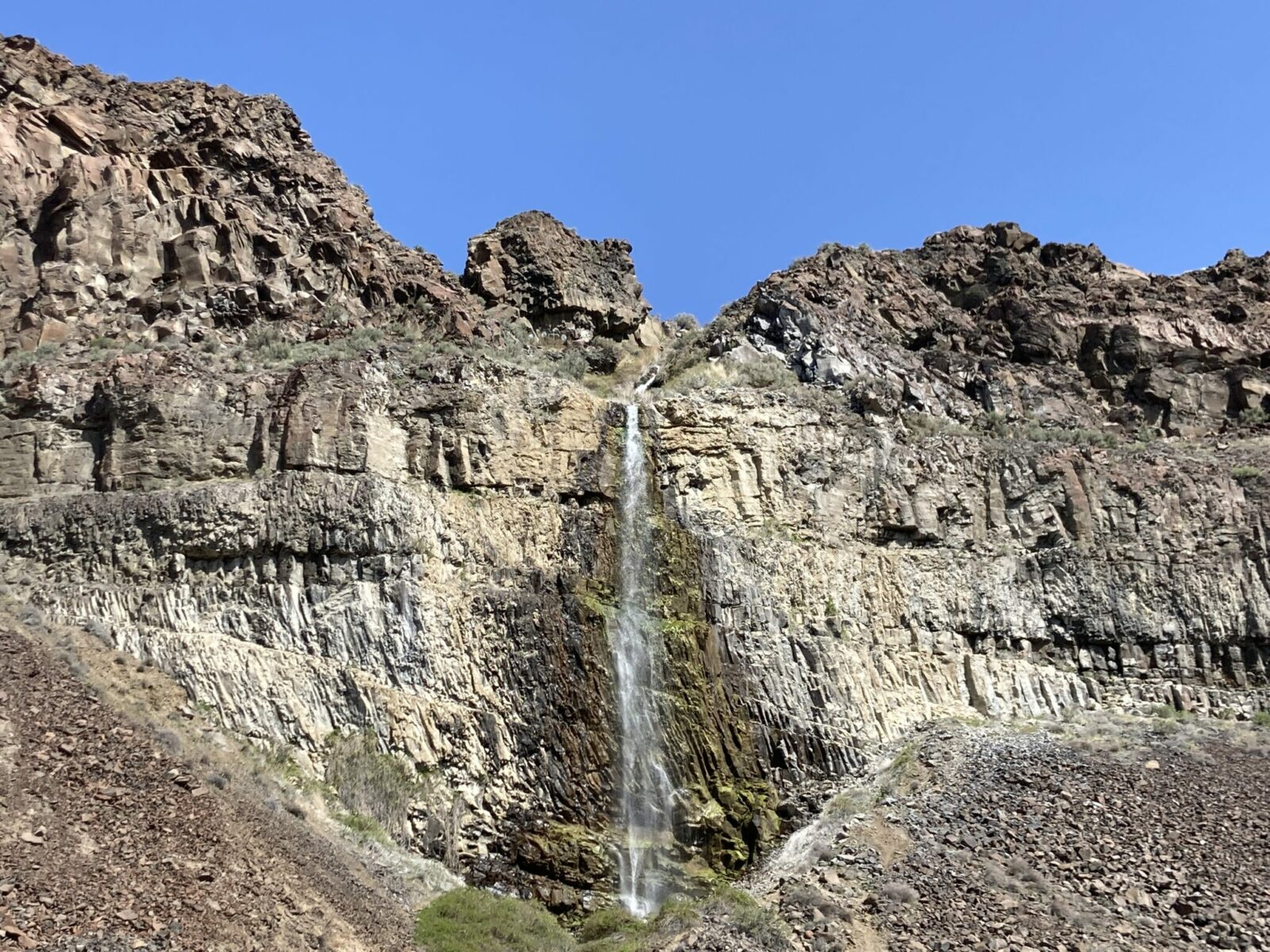 Narrow waterfall coming over vertical basalt rock on a sunny day in frenchman coulee