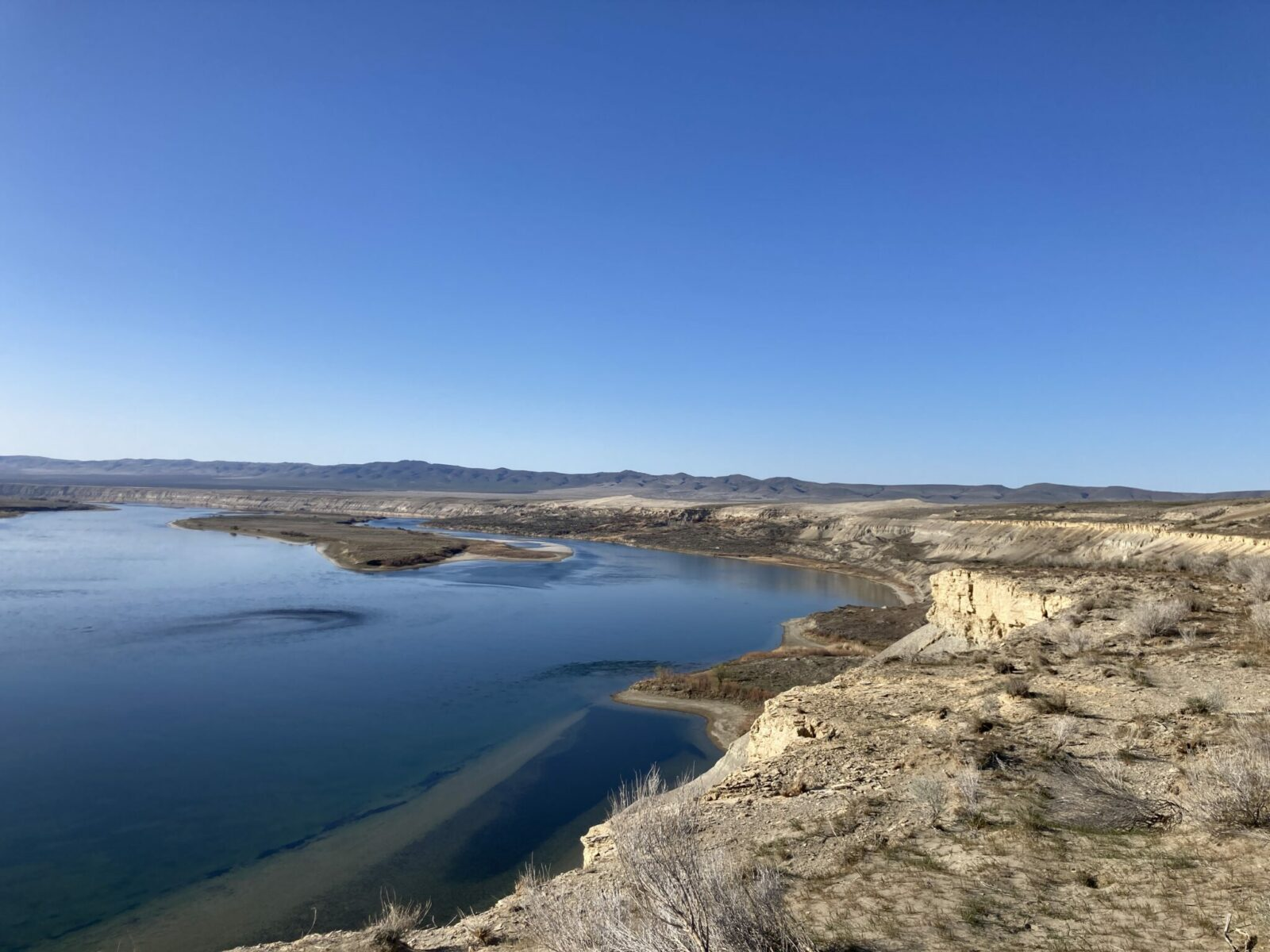 Hanford Reach is a section of the Columbia River in Eastern Washington. The river and an island in it are seen from the bluffs above, surrounded by bluffs and distant mountains on a sunny day