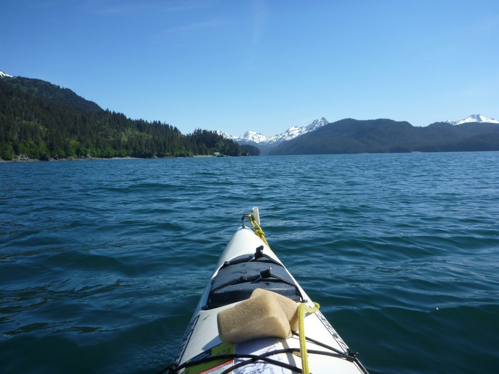 The front of a white kayak in Kachemak Bay near Homer, Alaska. There are high snowcapped mountains in the distance and forested hillsides
