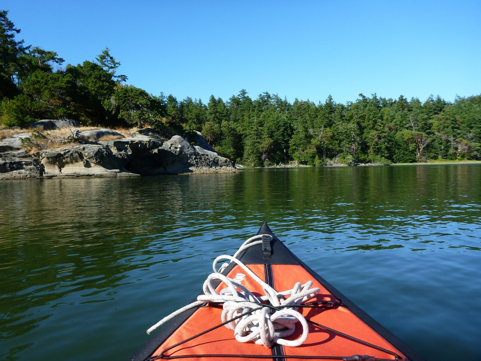 The front of a red kayak in Fossil Bay on Sucia Island. It's a sunny day and the forested island also has rocky outcroppings in the water