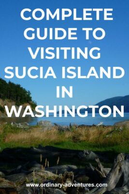 driftwood and grass at the head of a small bay surrounded by forests. Text reads complete guide to visiting sucia island in washington state